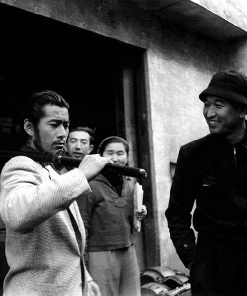 """Toshirō Mifune on the set of """"Seven Samurai"""" with director Akira Kurosawa. He carrying a real katana - the only type of sword he would use in his enactment as samurai in films. S)"""