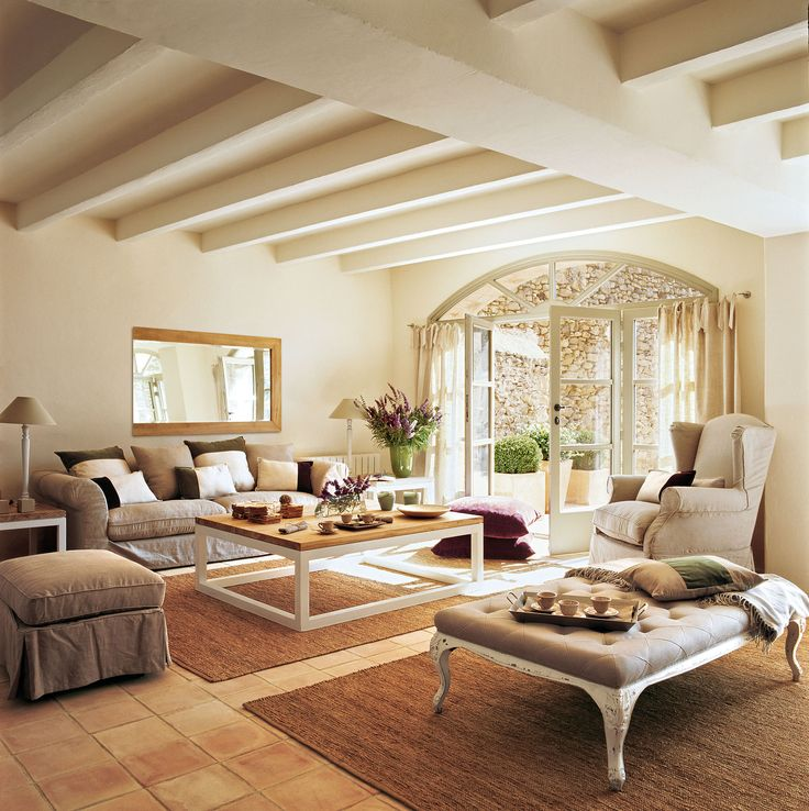 Salón en tonos beige con suelo de terrazo y puerta en arco