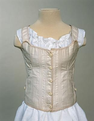 1880 Young Girl's Stays. White glazed twilled cotton, stiffened with close vertical groups of piping. Top and bottom edges bound with tape. Boned CF. Fastening with five bone buttons. Boned CB edges, lacing with cotton stay lace, and then ten metal eyelet holes each side. Shoulder straps sewn on.