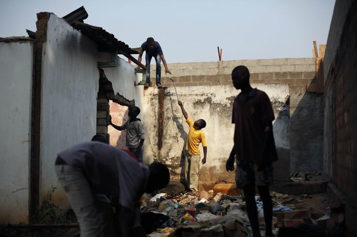Plunderaars halen het metalen dak van een moskee op het Plein van Verzoening in Bangui naar beneden.