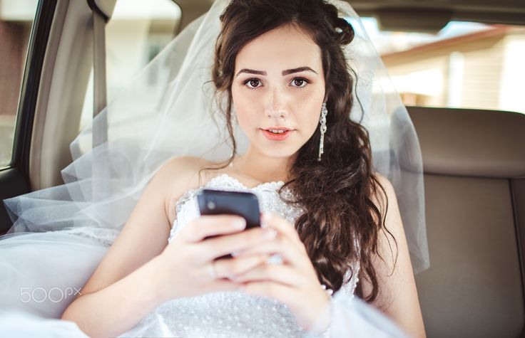 Beautiful bride sitting in car straight with mobile phone hairstyle and bright makeup. - Wedding: beautiful bride sitting in car straight with mobile phone hairstyle and bright makeup. Woman in white dress at wedding day waiting for groom and posing. Concept of love and interest. Newlywed