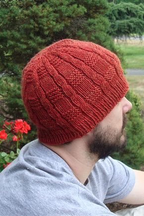 Image of a profile of a white male.  He's got a dark beard and is wearing a rusty red knit hat.