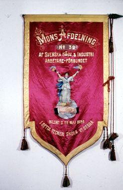 'MONS AFDELNING No 39 AF SVENSKA SÅGV. & INDUSTRI ARBETARE-FÖRBUNDET BILDAT D. 28 MAJ 1898 I DETTA TECKEN SKOLA VI SEGRA'. Baksidan har en lagerkrans på vit botten. Texten, målas i rött, lyder 'FRIHET JÄMLIKHET BRODERSKAP STANDARET INVIGT DEN 19 29/3 08 ENIGA VI STÅ SÖNDRADE VI FALLA'.