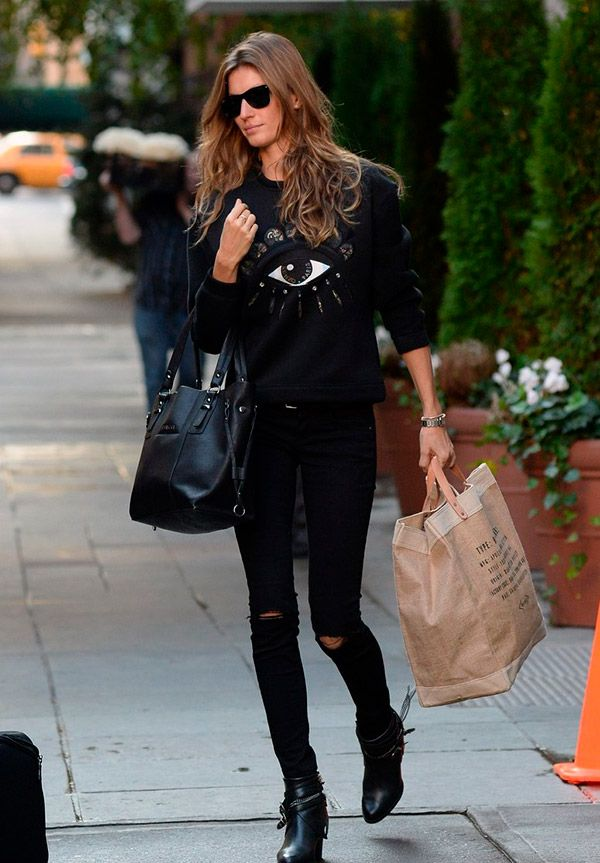 d915b6eec5cb2 O estilo de Gisele Bündchen é casual chic, ela usa look monocromático  preto, moletom estampado, calça skinny rasgada, bota com fivelas, óculos ray -ban ...