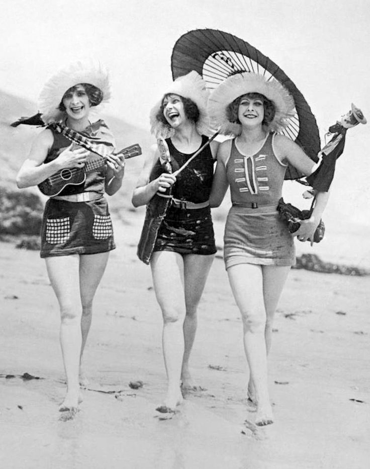 1920's beach fashion - (Credit: A frolicsome trio of American bathing beauties wearing the latest swimsuit costumes to the beach captured on film by English photographer E. O. Hoppe - Getty Images - http://www.gettyimages.no/detail/news-photo/frolicsome-trio-of-american-bathing-beauties-wearing-the-news-photo/50545085)