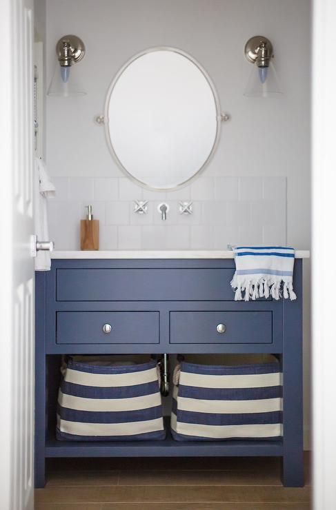 Blue and white cottage bathroom features a blue washstand finished with polished nickel knobs and shelves holding blue striped canvas bins and topped with a white quartz countertop fitted with a sink located beneath a polished nickel faucet mounted white square backsplash tiles under an oval pivot mirror flanked by glass cone shaped scones.