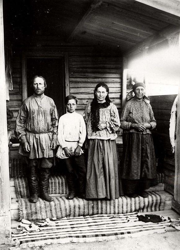 Крестьянская семья из д. Ловатской Канского уезда. Снимок сделан в д. Ловатской Канского уезда не позже 1905 г. Крестьяне в праздничной одежде стоят на ступеньках крыльца, застланного домоткаными половиками.