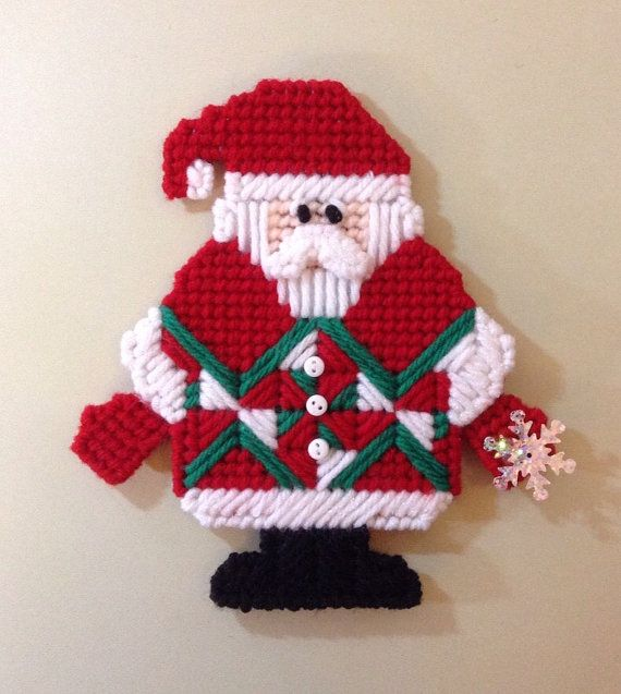 Santa Claus in red, green and white quilt block inspired style coat adorned with white buttons down the front. Wearing red mittens and black boots. Snowflake sequin in one hand.  Handmade plastic canvas Santa Ornament, Door Hanger, Wall Decor, Gift Tag  One sided ornament, back is covered with felt.  Size: Height: 6 inches tall Width: 5.5 inches (at widest points: mitten to mitten)  Contains small buttons, not a toy, for decorative purposes only.