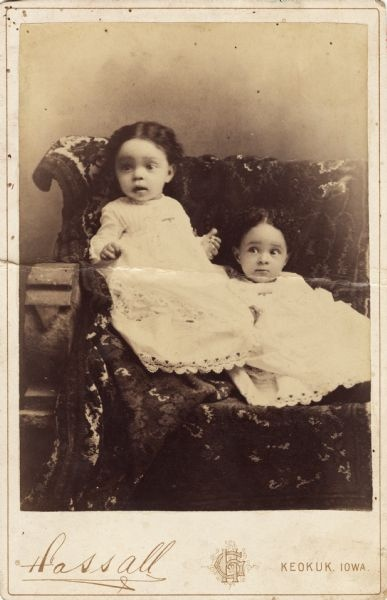Two cute African American little girls in white dresses trimmed with lace posing for a studio portrait on a bench covered with a kilim rug, c. 1885.