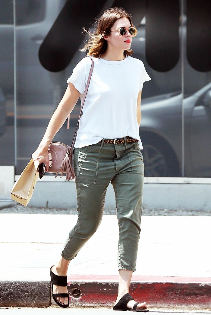 Mandy Moore wears a white t-shirt with cargo pants, black sandals, a pink leather bag, and sunglasses