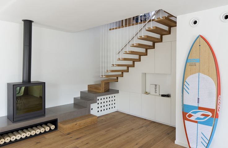 white home with oak parquet, wood stairs, fireplace on a concrete bench and... a red and blue surfborad