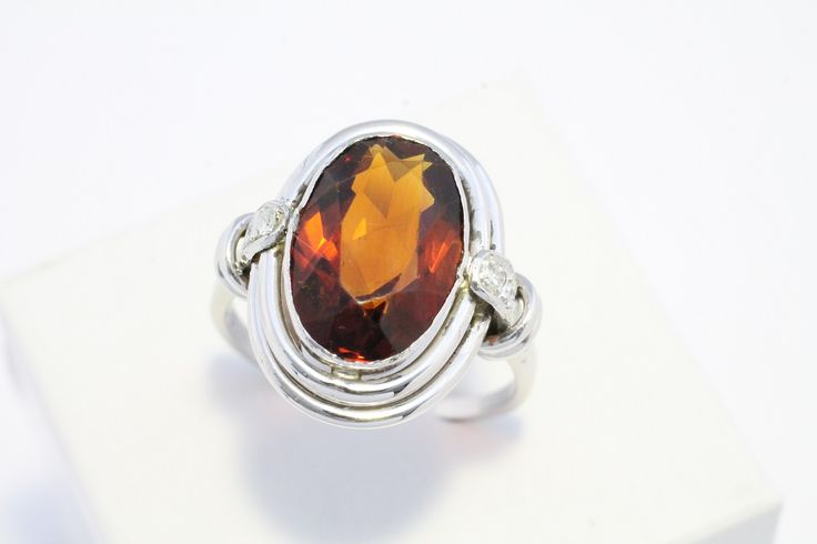 An oval faceted madeira citrine stone set in 14 carat white gold with four brilliant cut diamonds. The madeira citrine stones measures 1.3 cm by 9 mm. The ring has a date engraved on the inner shank with the year 1938.    Een ovaal gefacetteerde madeira citrien steen gezet in 14 karaat wit goud met vier briljant geslepen diamanten.  The Antique Ring Shop