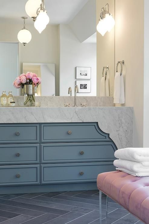Pink and Blue bathroom features a blue washstand topped with curved carrera marble under sconces ...