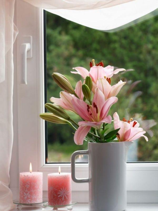 Розовые цветы и свечи на подоконнике