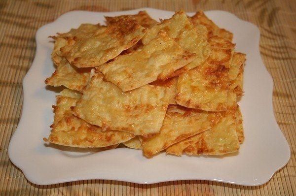 ЧИПСЫ ИЗ ЛАВАША   Ингредиенты  · 2 шт. лаваш (тонкий) · 200 г сметана · 300 г сыр (твердый) · 1 шт. яйца куриные · по вкусу перец черный · 3 зубчика чеснок  Приготовление:  Сыр натереть на мелкой терке, чеснок пропустить через пресс. Сметану взбить с яйцом, поперчить, добавить чеснок и 2/3 тертого сыра, перемешать. Листы лаваша смазать сырной массой, сверху посыпать оставшимся тертым сыром. Лаваш нарезать небольшими кусочками и выложить на сухой противень, запекать в духовке при 180 градусах…