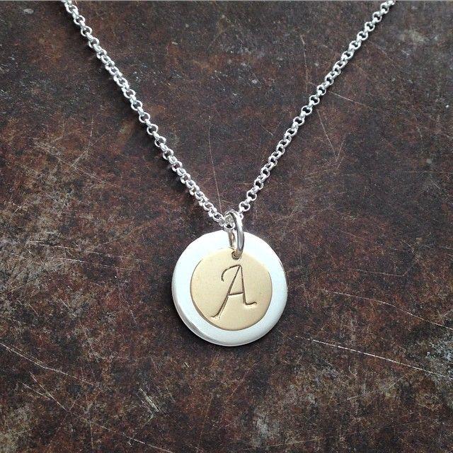 Initialsmykke i gull med et skjult hjerte i sølvplaten