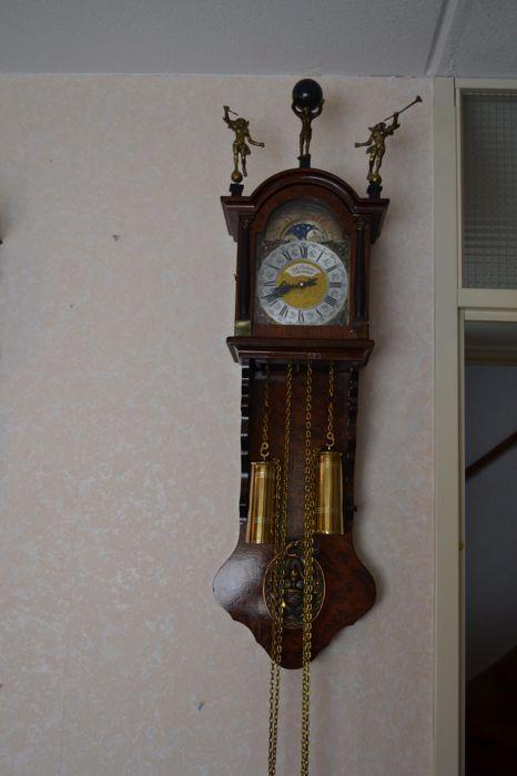 Friese Staart klok - Joh Duchesne Amsterdam - ca.1960  het is een Friese staartklok  met maanaanduiding .met afneembare staart en kap .de klok is gemaakt uit wortelnoten hout deze klok is gesigneert met: Joh Duchesne Amsterdam. en uitgevoerd met een zeer degelijk FHS uurwwerk( Frans Hermele & Son )op de kap staat atlas die de wereldbol draagt en 2 dazuinblazende engelen ( waarvan 1 van de bazuin ( trompet ) van de engel is helaas afgebroken ( zie foto ) maar dit is niet storend. de klok…