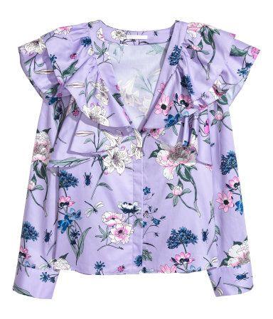 Lila/Geblümt. Gerade geschnittene Bluse mit großen Volants oben, V.-Ausschnitt und verdeckter Knopfleiste vorn. Lange, weite Ärmel mit eingelegten Falten