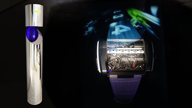 The HYT stand features long chrome tubes. The products are presented beneath transparent glass reflecting a holographic image.  HYT et ses tubes holographiques au SIHH 2017. Des longs tubes en chrome dressés sur le stand HYT. Les produits y sont présentés sous un verre transparent reflétant une image holographique.