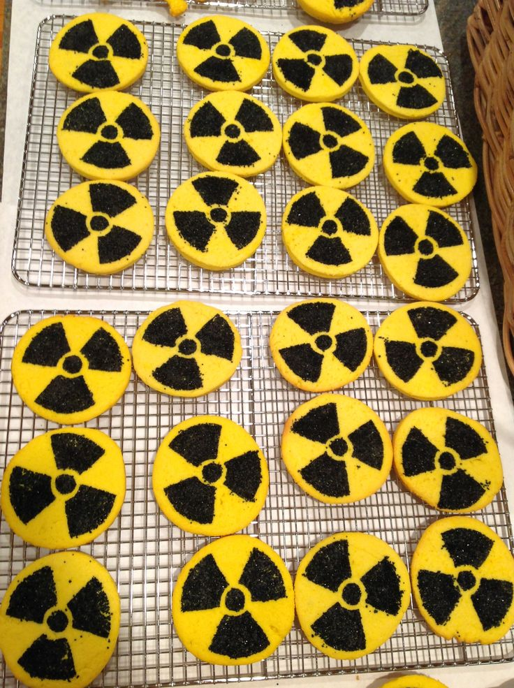 I made some yummy radioactive cream cheese cut out cookies for my Hubbies Godzilla themed birthday. I got an image of the radioactive symbol from the internet and made a stencil from an old plastic lid from a deli container. It is the same kind of plastic lid that is on coffee cans. I kept the lip of the lid up so the sugar wouldn't spill off of the lid. I lightly pressed the plastic stencil into the dough and rubbed the sanded sugar into the cookie dough then baked.
