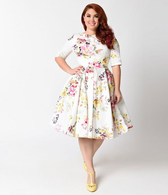 Made for a terrific caper! The Vintage Plus Size Hepburn dress has arrived fresh from The Pretty Dress Company in a beautiful ivory and signature floral Seville print, cast in a classic retro dress design! Darling details include a gorgeous high boat neck