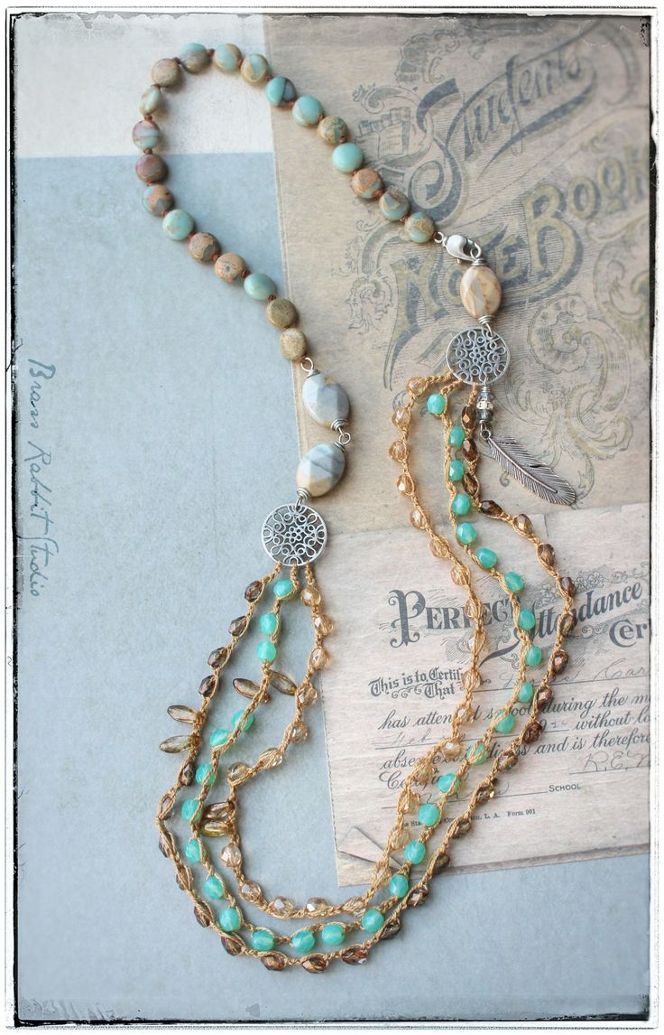 Triple strand Bohemian crochet and knotted necklace with hand made silver filigree connectors and feather charm, ocean jasper, serpentine, and three strands of crochet Czech glass crystals. Measures approximately 30""