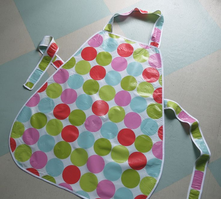 inexpensive vinyl tablecloth with flannel backing. Using an old apron as a pattern, lay out the tablecloth face down, trace the body of the apron with a marker and cut it out. Then cut two 25-inch strips for the ties and one 22-inch strip for the neck strap. use two packages of white double bias tape as seam binding and machine sew it to the edge of every piece. Then securely sew on the ties and neck strap to the reverse side of the apron body.