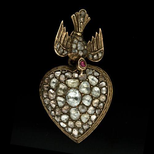 Late Georgian 14K yellow gold drop pendant featuring a diamond set bird motif with a ruby set head dangling a puffed heart encrusted with rose cut diamonds
