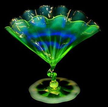 Opalescent Vaseline Glass fan-shaped vase in the Venetian style, possibly produced by the James Powell & Sons Whitefriars Glassworks, is shown illuminated under a blacklight. Photo courtesy LiveAuctioneers.com & Austin Auction Gallery