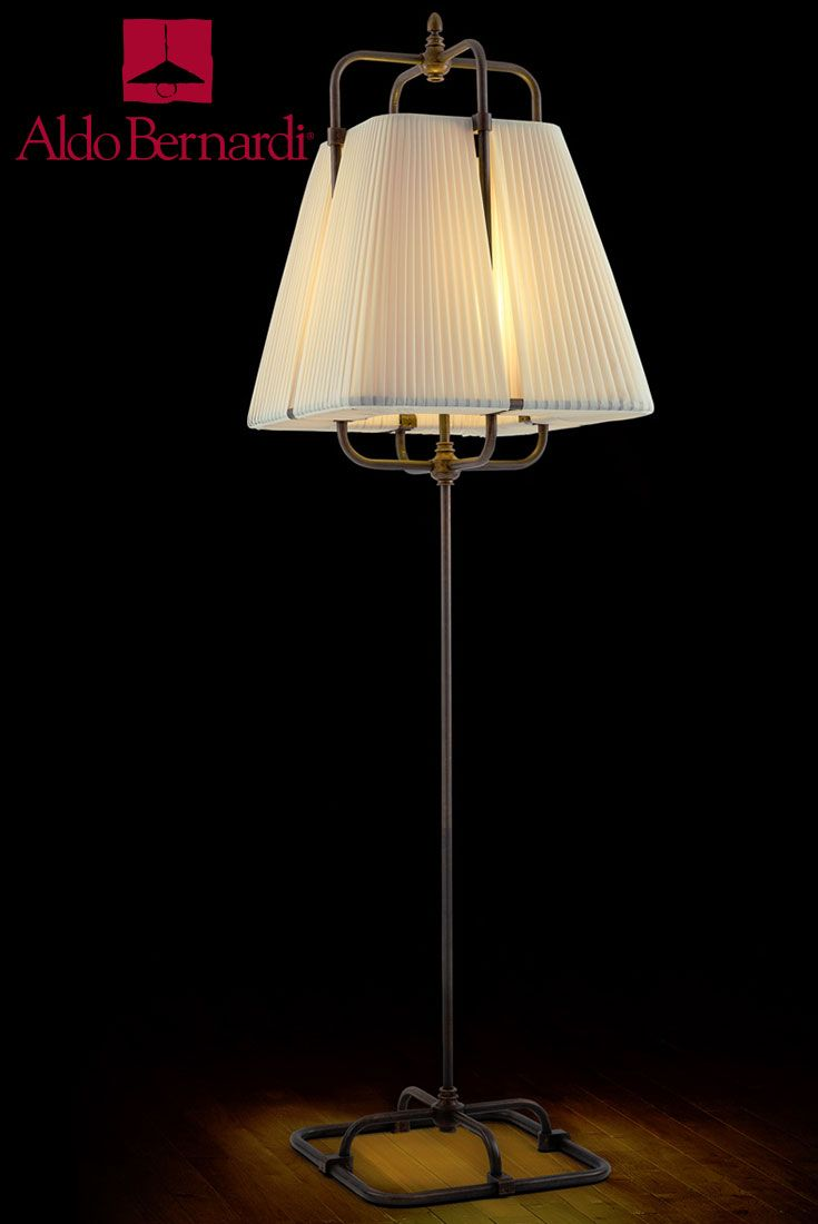 Moorea is a single stem antique brass mobile lighting fixture on square base with single light and fabric shade fully integrated into structure.