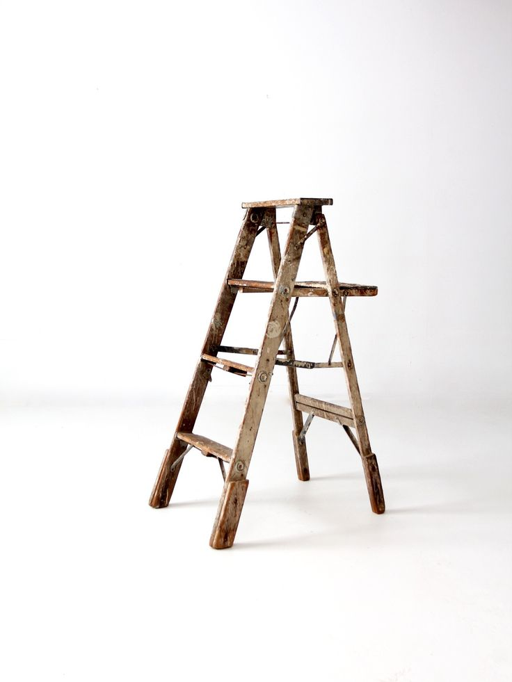 A vintage wood step ladder with heavy patina and paint splatter. The three rung ladder features wood base supports on the legs, and metal hinges and hardware. Incredible layers of paint color the ladd