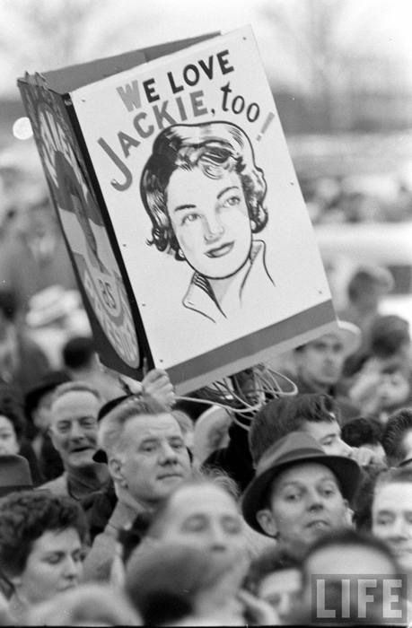 """Proud Kennedy campaigners for the 1960 election proudly parade the sign """"We love Jackie, too!""""."""