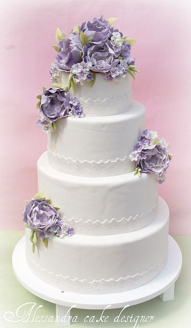 Beautiful lavender flowers are a perfect accent for this white cake with white…