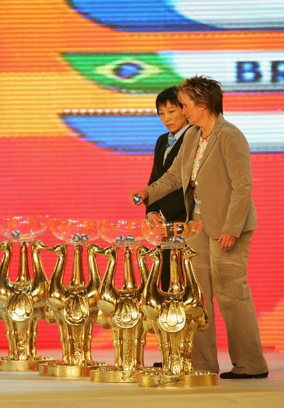 Tina Theune-Meyer (R), former coach of reigning world champions Germany, draws a team from the pot as FIFA women's football ambassador Sun Wen loo…