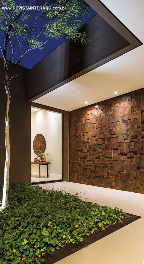 A parede revestida com mosaicos se une ao jardim na composição do hall de entrada