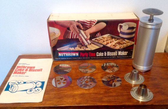 A NutBrown  Party Time Cake and Biscuit making set in its original 1950s box, with the instruction and recipe leaflet.. The set can also be used for icing cakes, making meringues and eclairs and piping mashed potato.  Set consists of 1 large plunger, 6 plates with different patterns and shapes , 2 nozzles and the recipe/instruction leaflet. I am not sure if there would originally have been 2 further plates ,as there are 2 empty slots inside the box...although the pictures on the outside ...