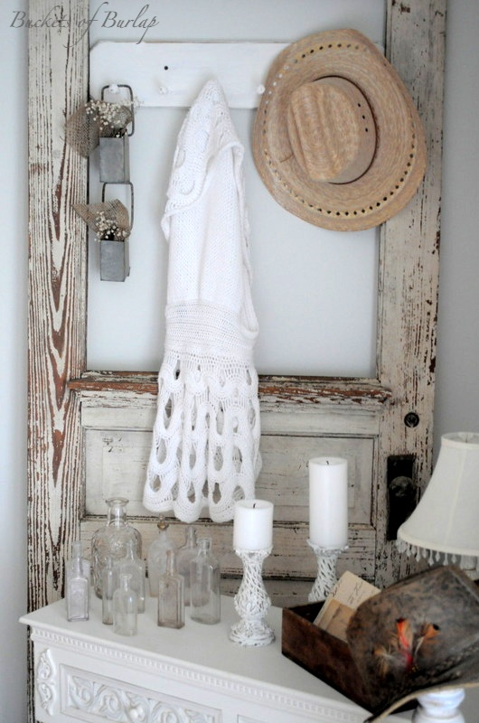 Old vintage door with worn white paint showing the grain repurposed as a hat and scarf rack...