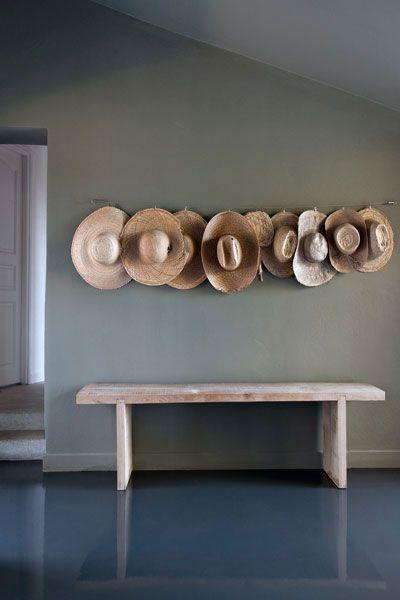 sol résine gris anthracite , mur a la chaux vert, banc en bois brut, chapeau de paille