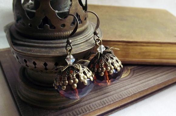 Mimosos brincos de cristais rondelle púrpura lapidados, translúcidos, com tons marrons, âmbar e roxos dependendo da incidência da luz. Eles foram decorados com tulipas e um pequeno cristal transparente no topo.  Comprimento: 3,5 cm