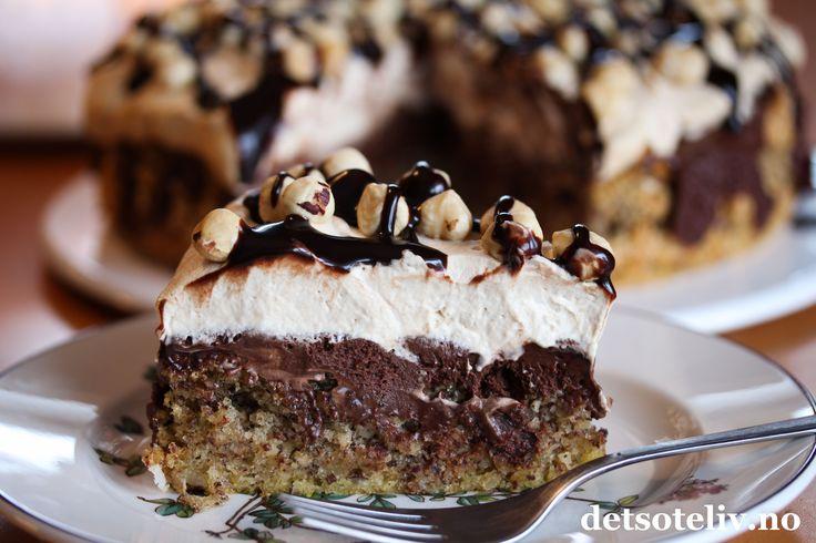 """Her er et herlig kaketips til helgen! """"Nøttekake med sjokolade og kaffekrem"""" er den mest leste oppskriften på NRK Mat i 2014! Jeg måtte såklart også teste kaken, og den var veldig, veldig god.  Kaken består av en meget myk nøttebunn som synker sammen i midten etter at den er ferdigstekt. Det passer bra, for gropen fylles med et deilig sjokoladefyll. På toppen dekkes kaken med luftig kaffekrem, som smaker deilig til resten. Jeg har pyntet kaken med hele hasselnøtter og sjokoladesaus, men…"""