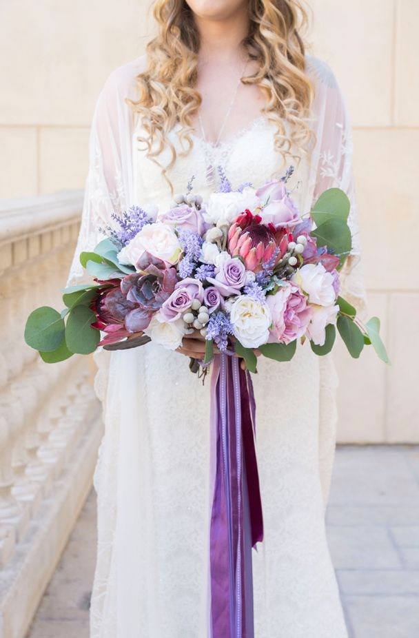 Boho rustic wedding bouquet with lavender, roses, peonies and protea tied together with a lilac purple ribbon | Peterson Design & Photography | See more on My Hotel Wedding: https://www.myhotelwedding.com/blog/2016/11/15/manhattan-beach-wedding-ayres-hotel