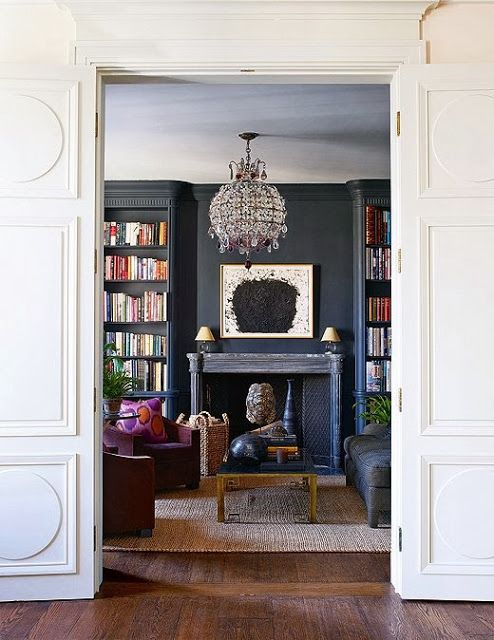 View from white panelled hall through to lovely dark walls (down pipe) in living room lounge