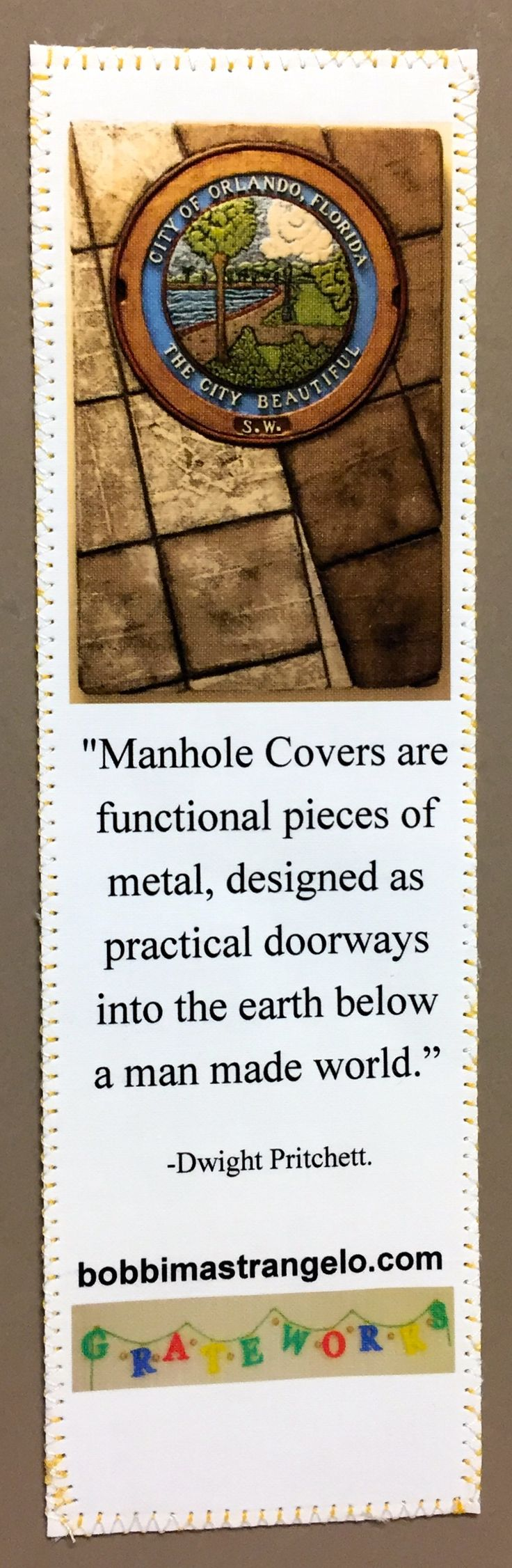 """Dwight Pritchett Quote printed on a book mark. Based on """"The City Beautiful"""" relief by Bobbi Mastrangelo and a Manhole Cover quote by Dwight Pritchett who was featured on Michelle Ward's 2016 October Manhole Madness. Solivita Quilter, Gaby Backert designed and sewed this Book Mark especially for Bobbi Mastrangelo, The Manhole Artist."""