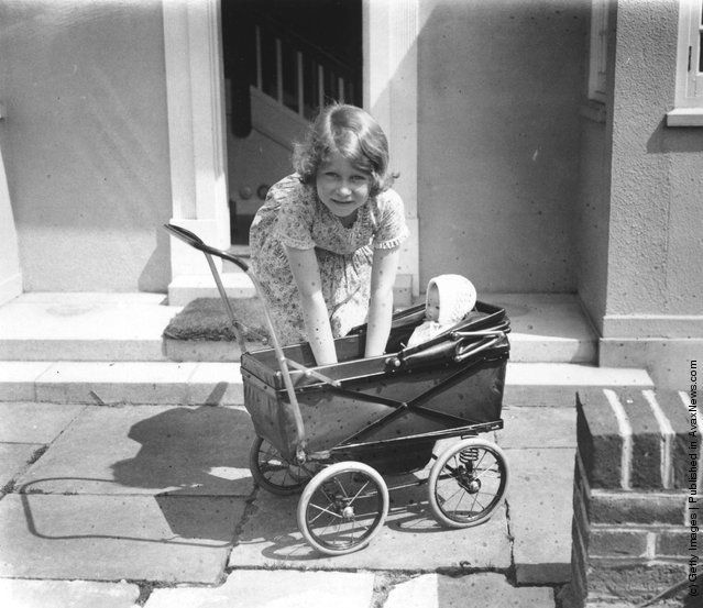 """indypendent-thinking: """"Princess Elizabeth playing with a doll in a toy pram outside the Welsh House, a miniature house presented to Princess Elizabeth and Princess Margaret by the people of Wales in..."""