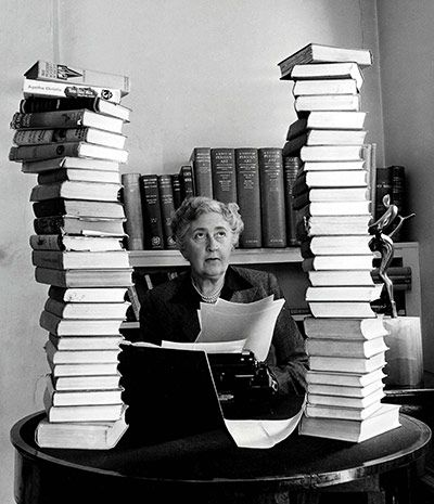 Agatha Christie -- mystery writer extraordinaire -- behind her desk with towers of her own books piled around her #authors #books MY FAVORITE AUTHOR OF ALL TIME!!! Second to God of course :-)