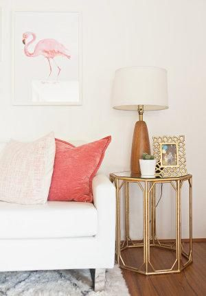 Pink and gold make for very pretty living room accents on top of an all-white and wood palette. The flamingo art and ornate open-work side table add a touch of whimsy!