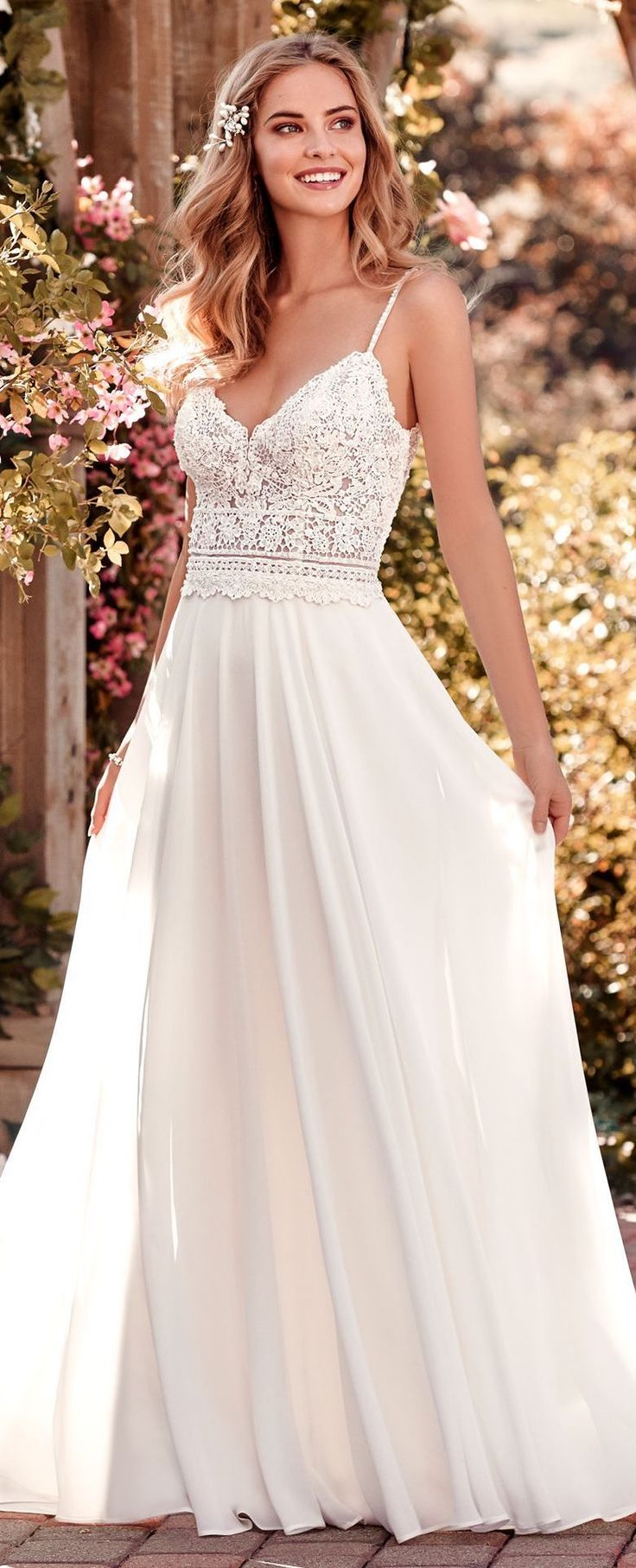 Wedding dress by Rebecca Ingram from Maggie Sottero. Chiffon boho-inspired wedding dress features a sheer bodice accented in beaded lace atop an Aria Chiffon skirt. A V-neck, V-back, and beaded spaghetti straps complete this sheath gown. Finished with cry