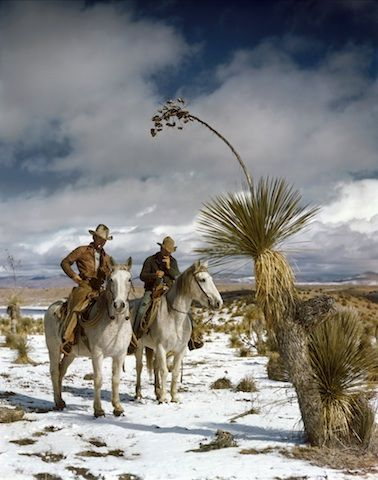 """""""Cowboys, New Mexico"""" Pigment print 1939 Ranching has been a relatively stable economic and cultural foundation for New Mexican communities for centuries. Bristol's image of two cowboys on horseback, probably from the McMillan ranch in Mangas Valley, captures the romance of ranching life. They are depicted riding through a recent snow in the high desert with an immense blue sky behind them."""