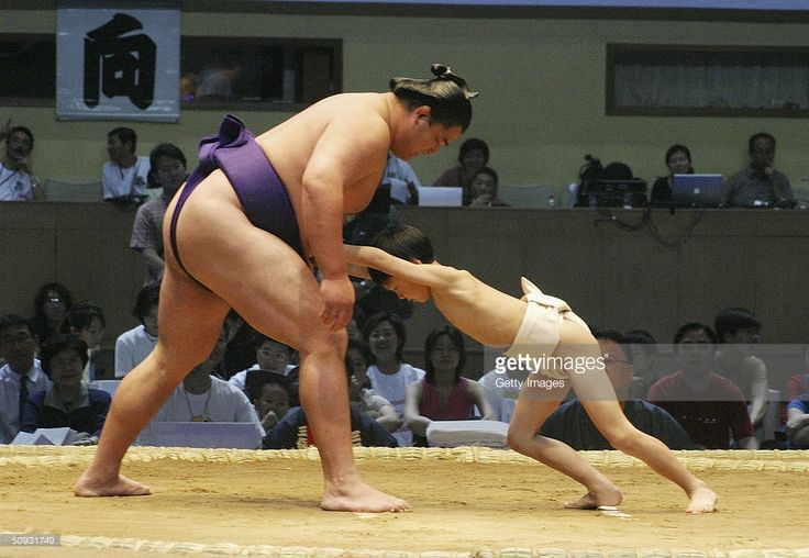 A little boy attempts in vain to 'fight' with a professional sumo wrestler during a pre-competition ceremony, on June 6, 2004, in Beijing, China. A total of 111 sumo wrestlers are in Beijing for demonstrations of the Japan's traditional sport. It is the first time in thirty years that sumo wrestlers perform in China.