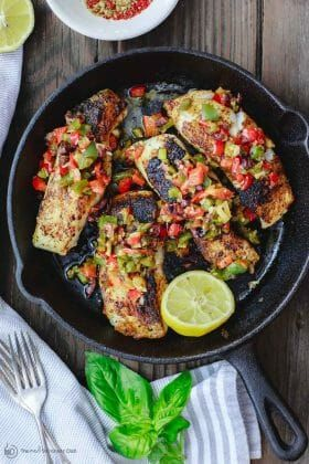 Mediterranean Pan Seared Sea Bass Recipe | The Mediterranean Dish. Quick and crispy pan seared sea bass, coated with Mediterranean spices and a tasty bell pepper medley to serve on top or as a side! Dinner in minutes! from TheMediterraneanDish.com #mediterraneandiet #mediterraneanrecipes #seafoodrecipes #fish #fishrecipes #healthyrecipes #lowcarbrecipes #weeknightdinner #weeknightmeal #onpotdinner #onepan #glutenfreerecipes #seabass #easyrecipes